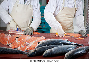 Workers Slicing Fishes At Table - Midsection of workers...