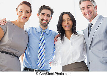 Workers smiling while standing together