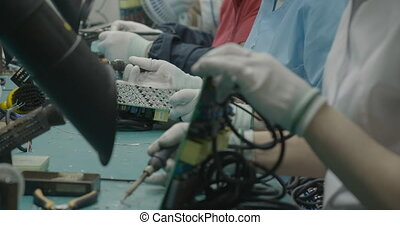 Workers soldering circuit board closeup