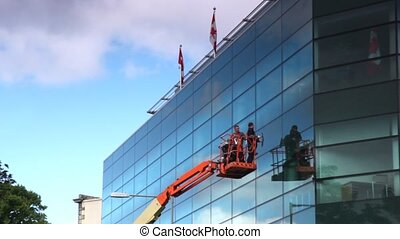 workers standing on crane washing glass building with two flags on top