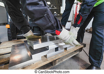 Workers taking aluminium billet
