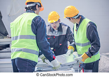 Workers taking aluminium billet at CNC machine shop