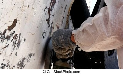 Workers tear off paint on metal in repairs process at...