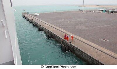 workers ties mooring line of ship to moorage - four workers...