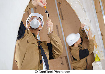 workers together demolishing a wall