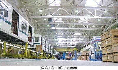 Workers unload loaders in workshop of engineering plant,...