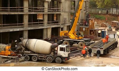 Workers unload truck with metal wires using crane, concrete...