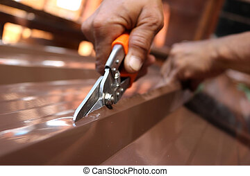 Workers use scissors to cut the metal sheet for roofing