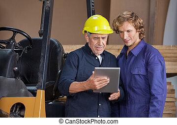 Workers Using Digital Tablet In Workshop