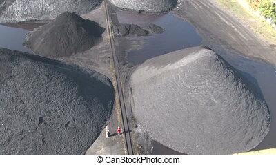 Workers walk between heaps of coal