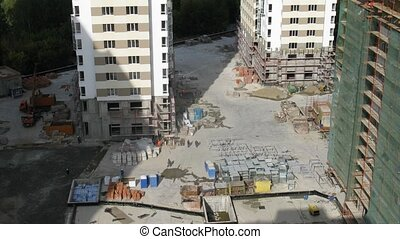 Workers walk on building site in housing estate below, time...