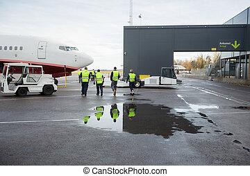 Workers Walking Towards Airplane On Wet Runway