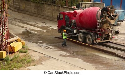 Workers wash concrete mixer - Two workers wash concrete...