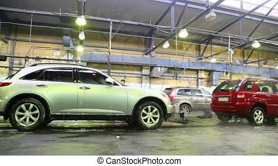 Workers wash with streams of water some cars on car wash
