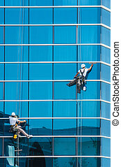 workers washing windows of the modern building - workers...