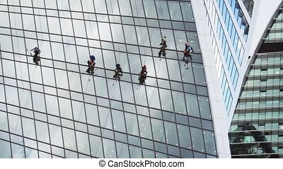 Six laborers dangle high above the ground, washing the windows of an enormous, highrise building in Moscow, Russia.