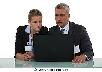workers wearing badge in front of a computer