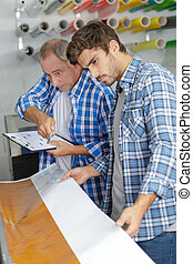 workers with a large printer format inkjet working