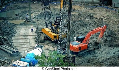 Workers With Cement Mixer On Site
