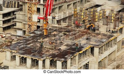 Workers with heavy machinery build one of house floors