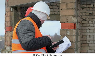 Workers with tablet PC and tape measure near the building