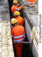 workers with yellow helmet inside the trench of road...