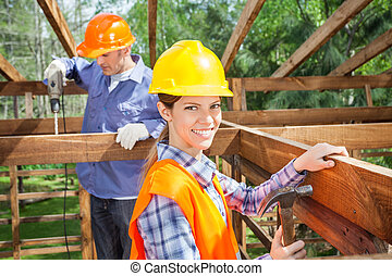 Workers Working In Timber Frame At Site