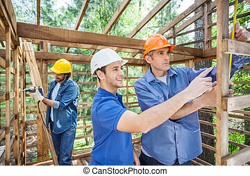 Workers Working In Wooden Cabin At Site - Male workers...