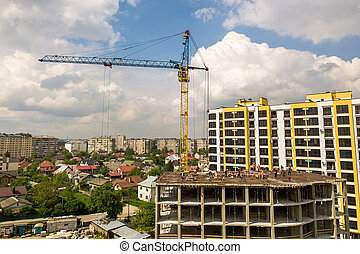 Workers working on concrete frame of tall apartment building under construction in a city.