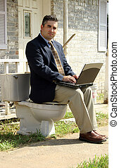 Workflow - Man in suit with laptop sitting on toliet outside...