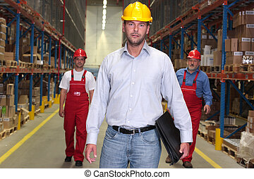 boss with briefcase at the front of team of workforce in warehouse - 2 workers in background