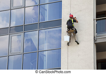 Working at height - Building maintenance: Man working at...