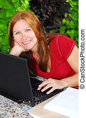 Working at home - Happy mature woman working on portable...