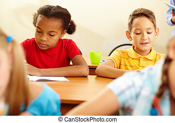Working at lesson - Portrait of cute schoolkids working at...