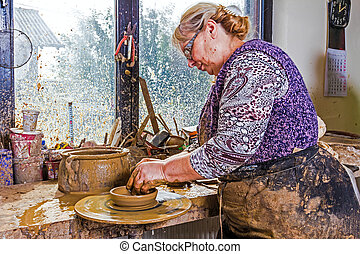 Working at pottery wheel