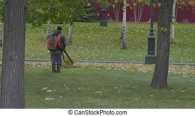 Working blows autumn leaves vacuum blower
