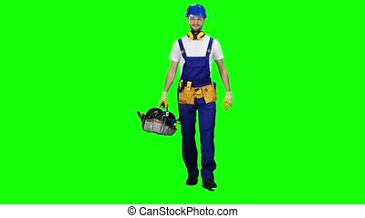 Working builder goes to work with a suitcase with tools. Green screen
