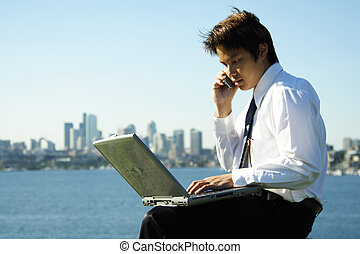 Working businessman - A businessman working outdoor at a...