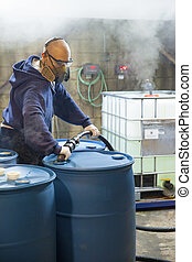 Chemical Plant. Man working in protective gear, safety glasses, respirator, and gloves, blends chemicals in 55 gallon drums. Gasses from chemicals emit from the containers. Corrosive Environment.