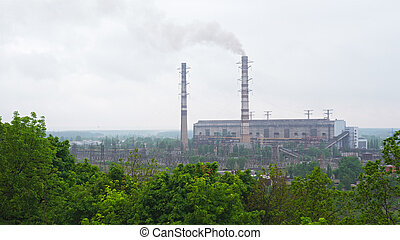 Working coal-fired power plant with high tubes and smoke on...