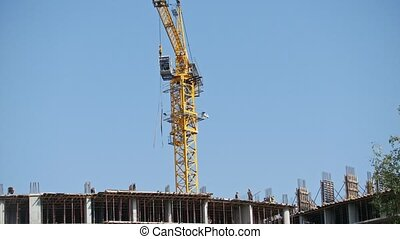 Working crane at construction site - modern living building -workers