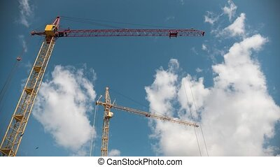 Working crane in construction site in fronr of blue sky, time-lapse