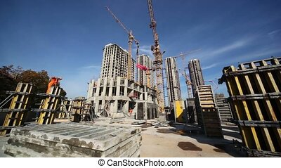 Working cranes inside place for with buildings under construction