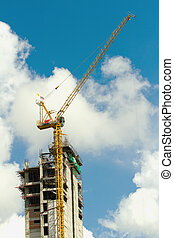Working cranes inside with tall buildings under construction under a blue sky