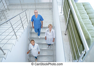 Team of smiling medical workers going downstairs