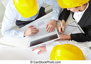 Working engineers - Three engineers in helmets working with...