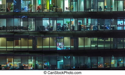 Working evening in glass office building with numerous offices with glass walls and windows timelapse