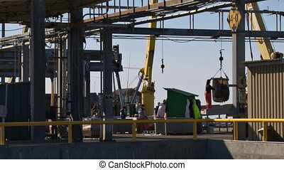 A day on the fish docks. Halibut boat being offloaded by crane and bucket to the fish sorting and packing crew while another boat moves away.