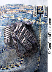 working glove in the back pocket of old used jeans