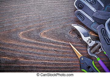 Working gloves metal garden shears pruner on wooden board.